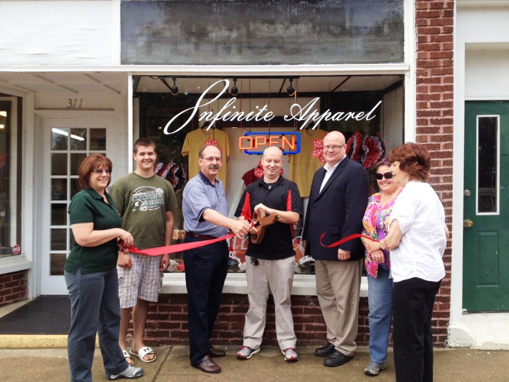 Owner Dave Lamp cuts the ribbon at Infinite Apparel.  (l - r) Lovedia Stap (Chemical Bank), Bryce Frost (Stop The Bullying Now) Phil Siegler (Bartz Rumery) City Manager Rob Hillard, Kass Hillard (Allegan Artisans Market), and Mayor Nancy Ingalsbee